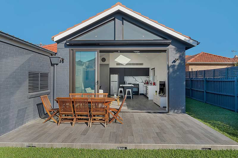 Modest exterior expansive interior Maroubra addition - courtyard looking in to kitchen