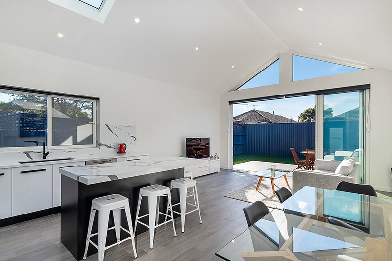 Modest exterior expansive interior Maroubra addition - kitchen to garden